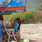 Children play in the shade of a water truck. (Photo by Leny Olivera)